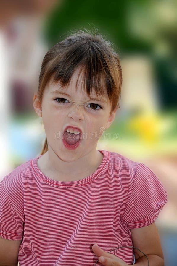 女孩起皱纹她的鼻子和大声呼喊 免版税库存图片
