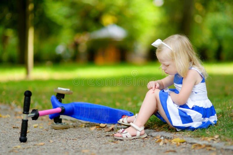 女孩跌倒了,当乘坐她的滑行车时 免版税库存照片
