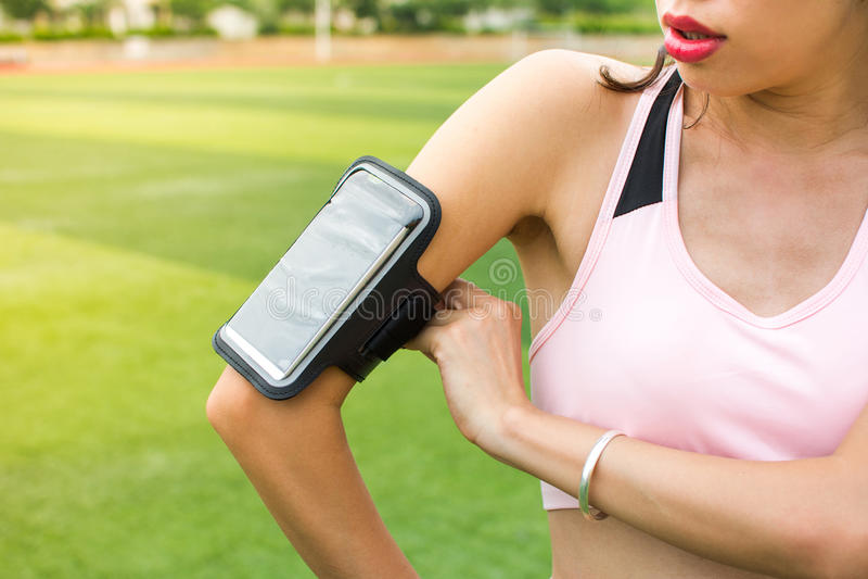 女孩跟踪跑步的活动的安装智能手机 免版税图库摄影