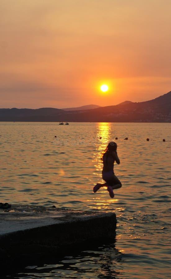 女孩跳到水的,在契奥沃岛海岛上的日落在特罗吉尔市附近的克罗地亚,达尔马提亚 免版税库存照片