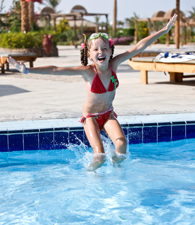 女孩跳池红色游泳泳装 库存图片