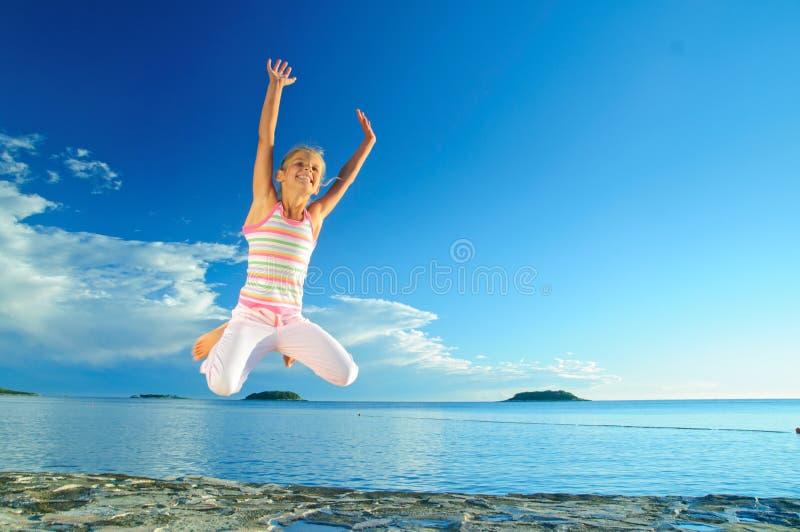 女孩跳海运 免版税图库摄影