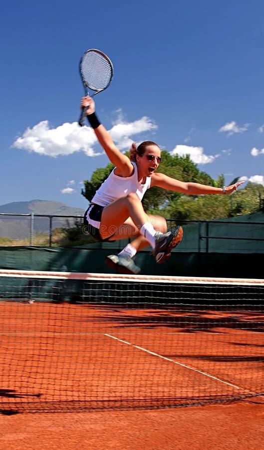 女孩跳的净网球 免版税库存照片