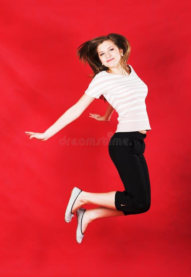 女孩跳跃在红色的喜悦 库存照片