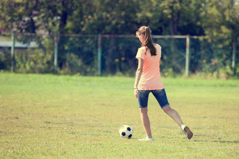 女孩踢球的运动员踢了足球 免版税库存图片