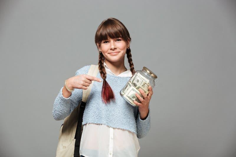 女孩身分隔绝了与瓶子的灰色背景有很多金钱 免版税图库摄影
