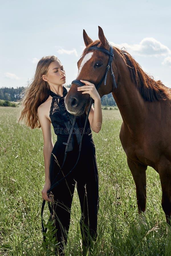 女孩车手在领域的马旁边站立 妇女的时尚画象和母马是马在草的村庄 免版税库存图片