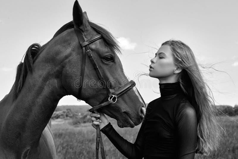 女孩车手在领域的马旁边站立 妇女的时尚画象和母马是马在草的村庄 免版税图库摄影