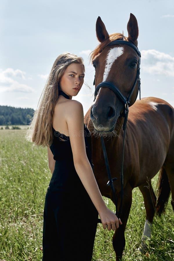 女孩车手在领域的马旁边站立 妇女的时尚画象和母马是马在草的村庄 库存图片