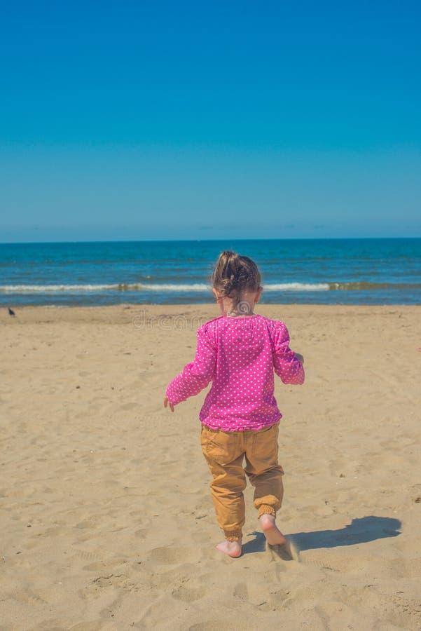 女孩转动了并且跑了在海滩下 一件桃红色毛线衣的一女孩有白色圆点和沙子色裤子的 免版税库存照片