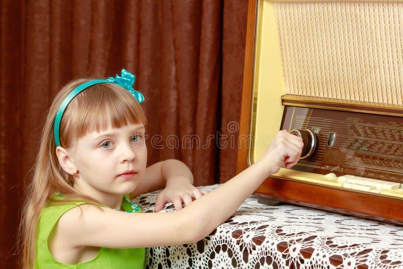 女孩转动在老收音机的容量瘤 减速火箭的样式 免版税库存照片
