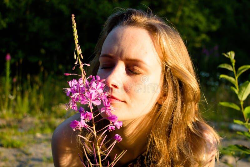 女孩轻轻地接触她的鼻子到花并且吸入他的精美芬芳 在一个夏天晴天,光芒在她的gen落 库存照片
