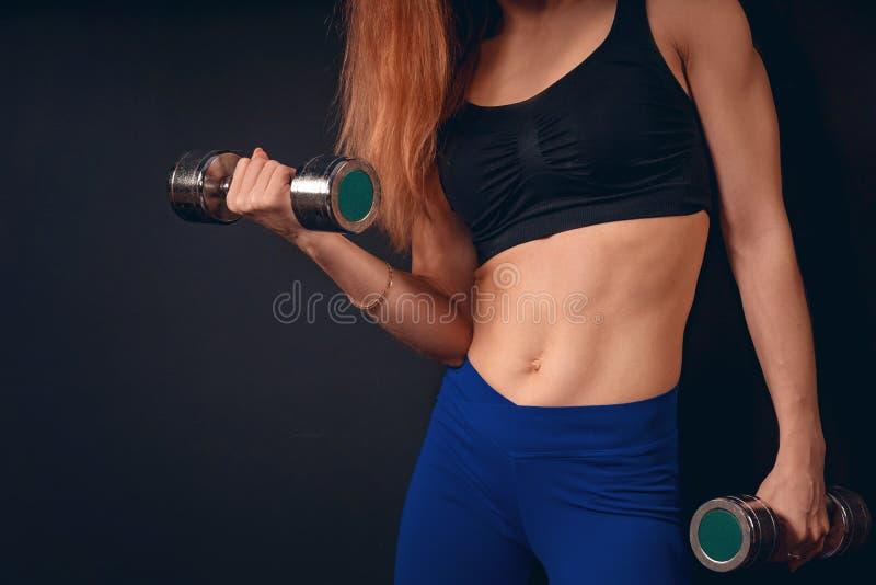 女孩运动推力哑铃 二头肌的锻炼与哑铃 免版税图库摄影