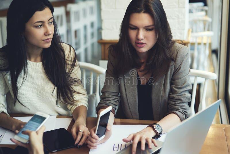 女孩运转一起解释的名牌服装要求并且分配给同事通过便携式计算机被连接到wifi 免版税库存照片