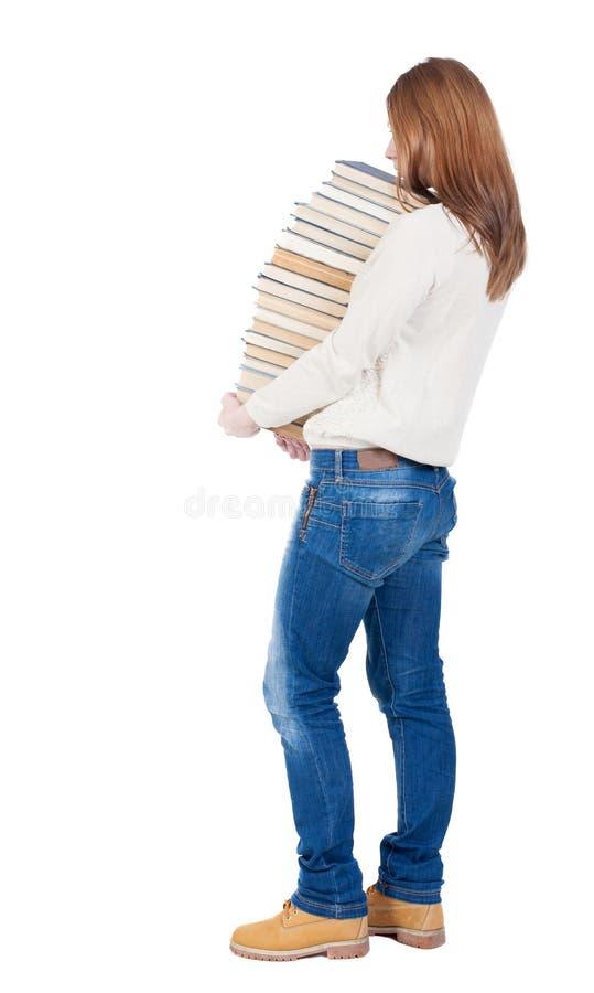 女孩运载重的堆书 回到视图 背面图peopl 免版税库存照片