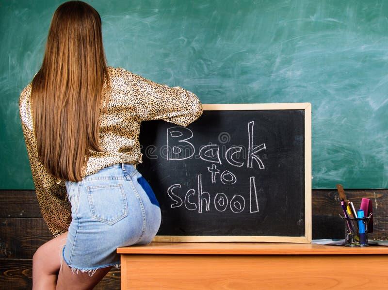 女孩违反学校衣物规矩的牛仔布裙子 学校着装条例 后面和屁股学生在黑板附近 学生 免版税库存照片