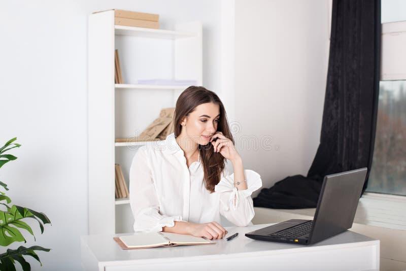 女孩连接到互联网通过膝上型计算机 女孩在家工作-一位自由职业者 有吸引力的办公室工作者身分 Positi 免版税图库摄影