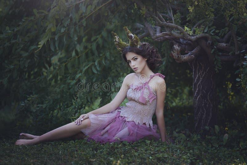 女孩迷惑了有坐在树下的垫铁的公主 在破旧的衣裳的女孩神秘的生物小鹿在一个神仙的森林里 免版税图库摄影
