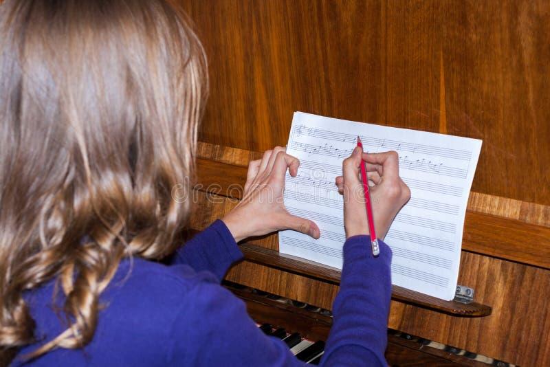 女孩选址在钢琴并且写着音符 库存照片