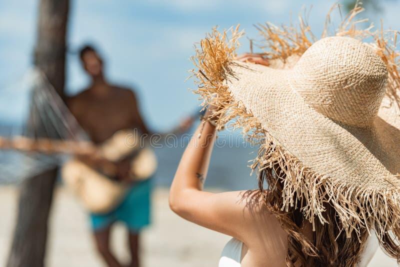 女孩选择聚焦弹声学吉他的草帽和人的 免版税图库摄影