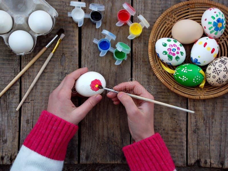 女孩递与花卉样式树胶水彩画颜料的绘画鸡蛋 装饰鸡蛋 背景面包软绵绵地结块复活节彩蛋酥皮点心准备影子白色 免版税库存图片