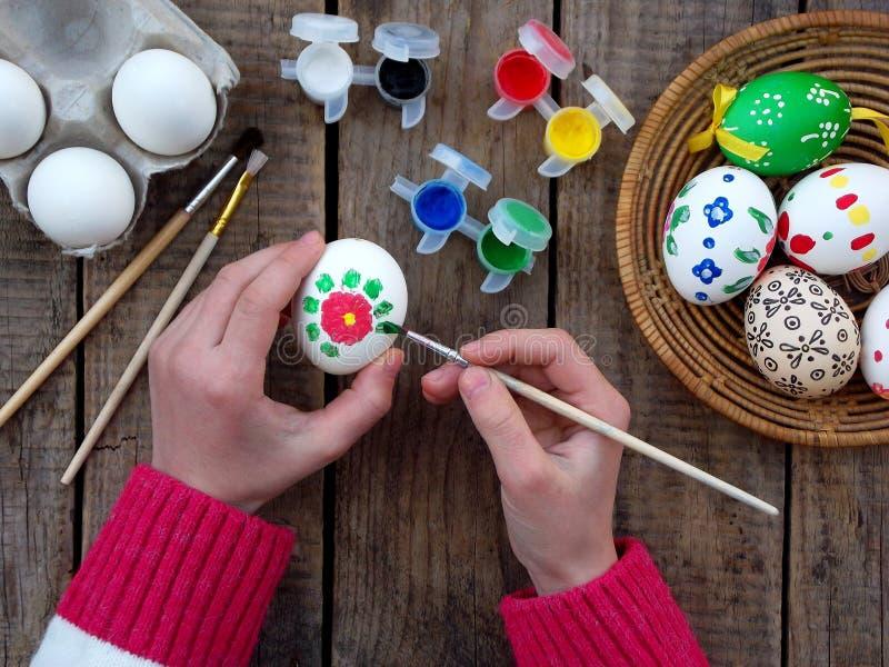 女孩递与花卉样式树胶水彩画颜料的绘画鸡蛋 装饰鸡蛋 背景面包软绵绵地结块复活节彩蛋酥皮点心准备影子白色 免版税库存照片
