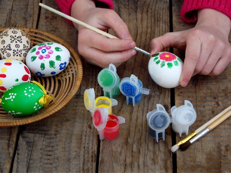 女孩递与花卉样式树胶水彩画颜料的绘画鸡蛋 装饰鸡蛋 背景面包软绵绵地结块复活节彩蛋酥皮点心准备影子白色 库存图片