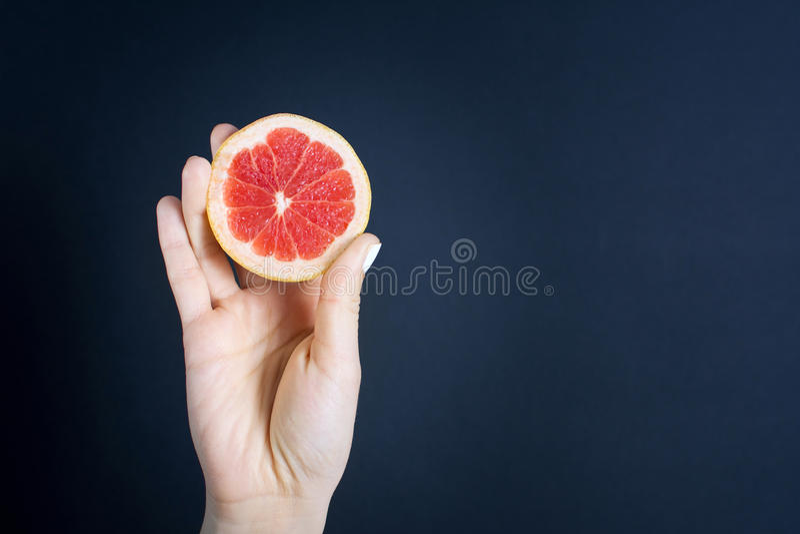 女孩递拿着一个被对分的葡萄柚 库存照片