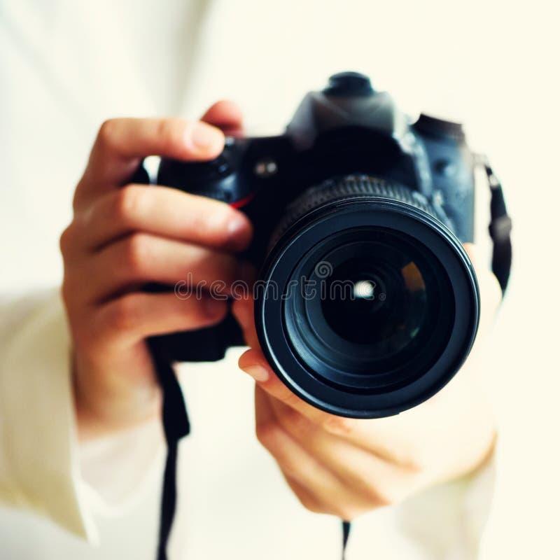女孩递拿着照片照相机,白色背景,拷贝空间 旅行和射击概念 方形庄稼 库存照片