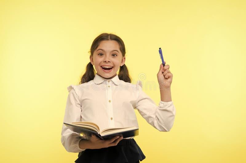 女孩逗人喜爱的女小学生在一致的举行书或课本黄色背景中 努力学生从书得到知识 ?? 免版税库存照片