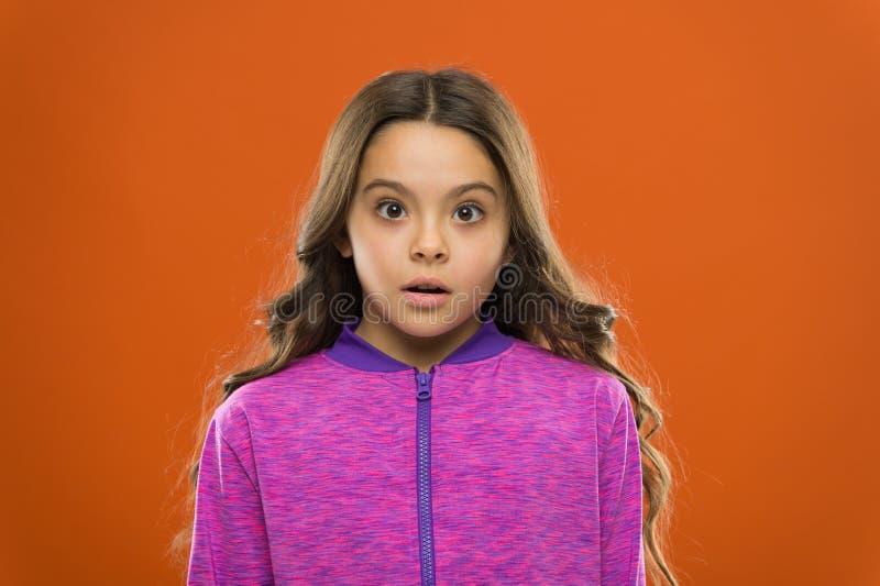 女孩逗人喜爱的孩子被混淆的想知道的面孔 儿童长发想知道 混淆的事实概念 将吹您的事实 图库摄影