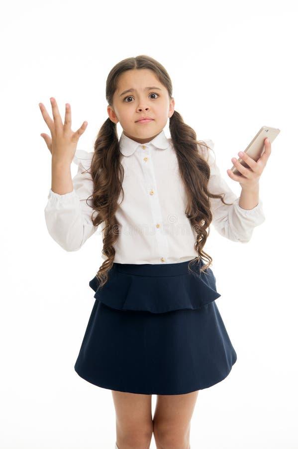 女孩逗人喜爱的长的卷发拿着智能手机白色背景 儿童绝望无能为力的面孔表示拿着智能手机 免版税库存照片
