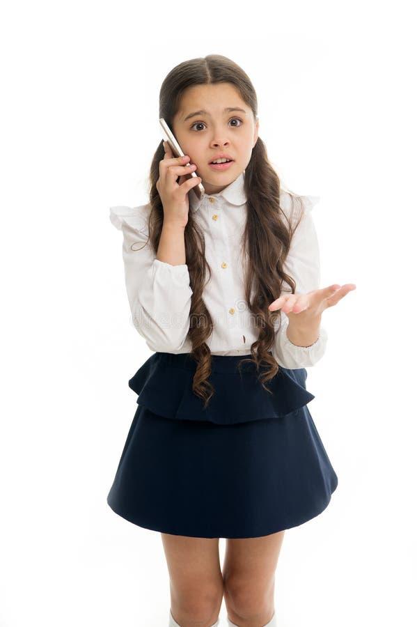 女孩逗人喜爱的长的头发谈话智能手机白色背景 儿童绝望无能为力的面孔表示讲智能手机 免版税库存照片