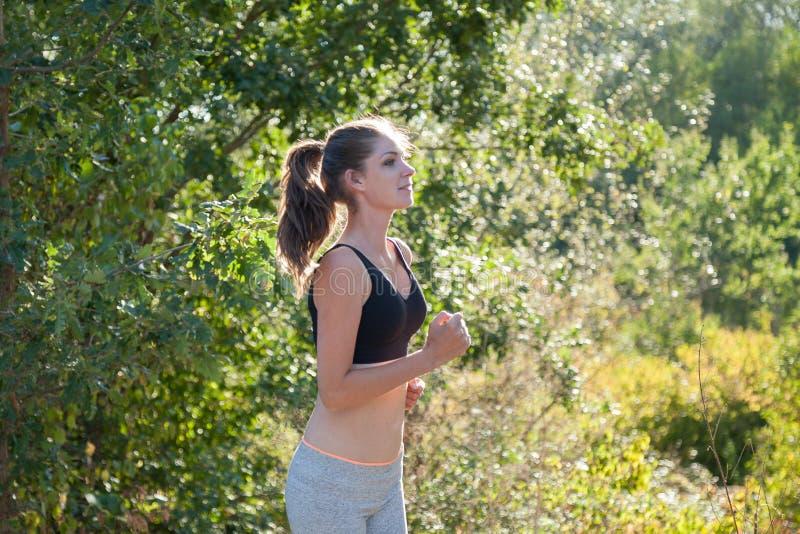 女孩通过森林跑步的锻炼体育跑 免版税库存照片