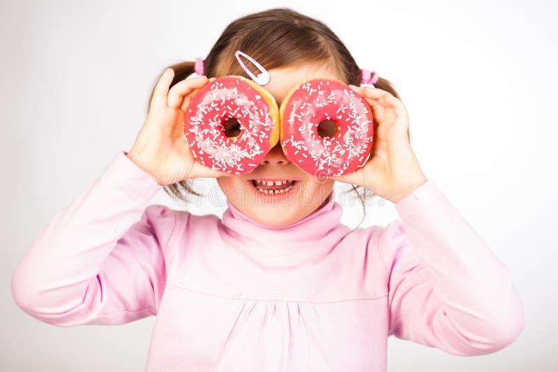 女孩通过油炸圈饼查找 图库摄影