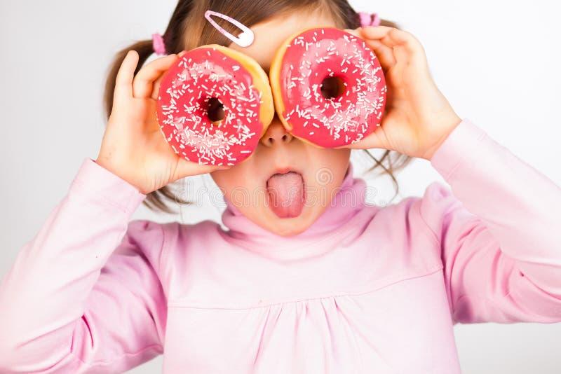 女孩通过油炸圈饼查找 免版税库存照片