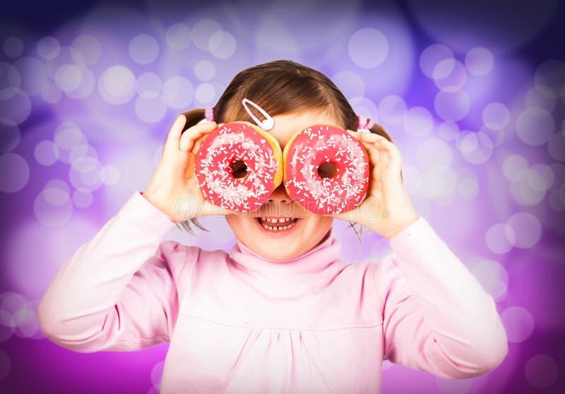 女孩通过油炸圈饼查找 免版税库存图片