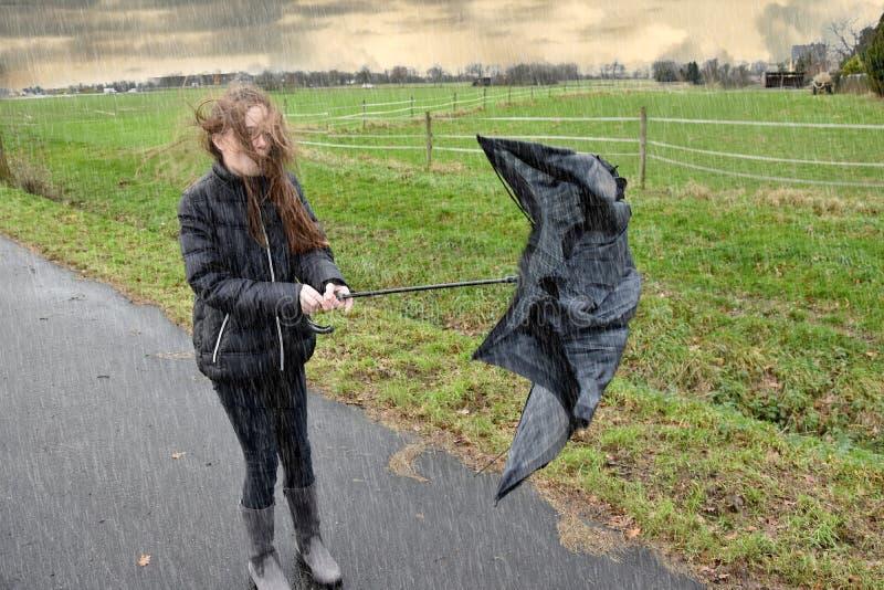 女孩通过雨走,并且风暴,她的伞是残破的 库存图片