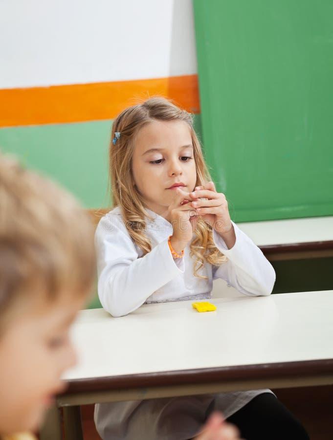 女孩造型黏土在教室 库存照片