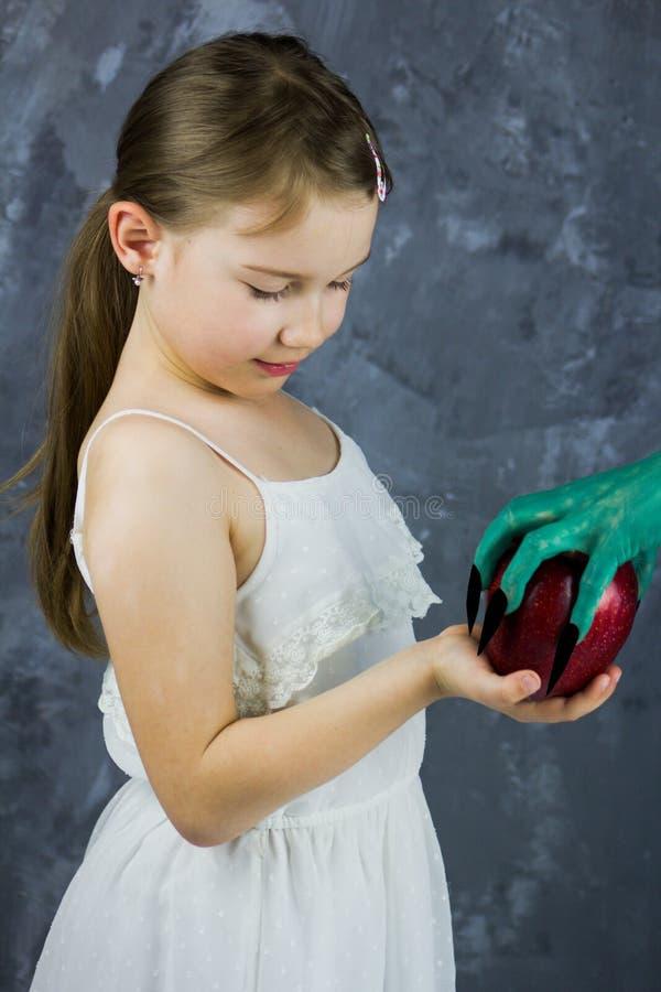 女孩采取从巫婆的一个苹果 雪白童话 免版税库存图片