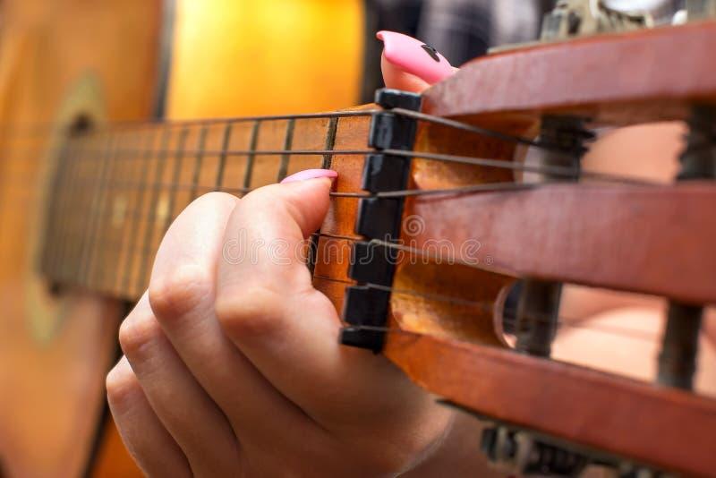 女孩采摘夹紧在fretboard的弦苦恼 夸大吉他关闭的女性妇女手 免版税库存照片