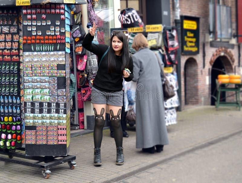 女孩采摘纪念品磁铁在阿姆斯特丹 免版税图库摄影