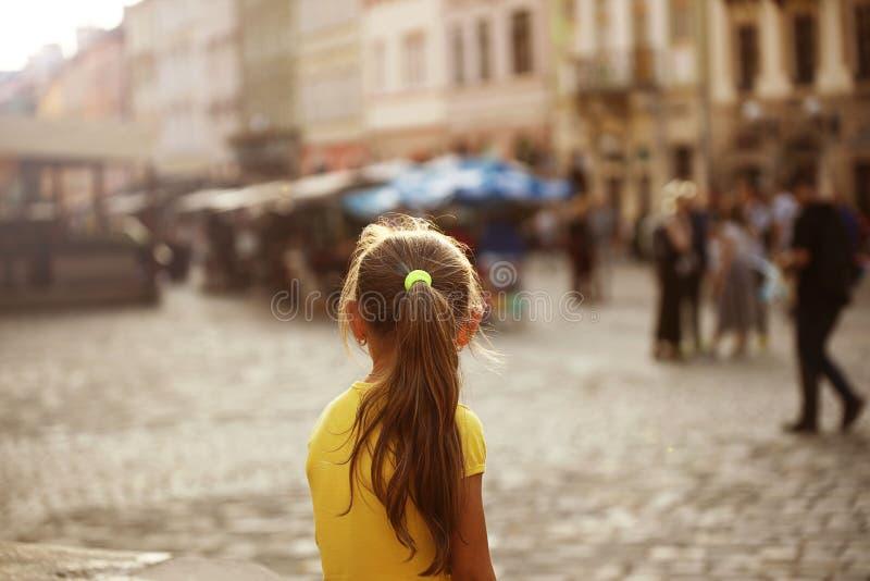 女孩金发碧眼的女人调查在中世纪欧洲城市的街道上的距离身分 一点旅客 市中心 库存照片
