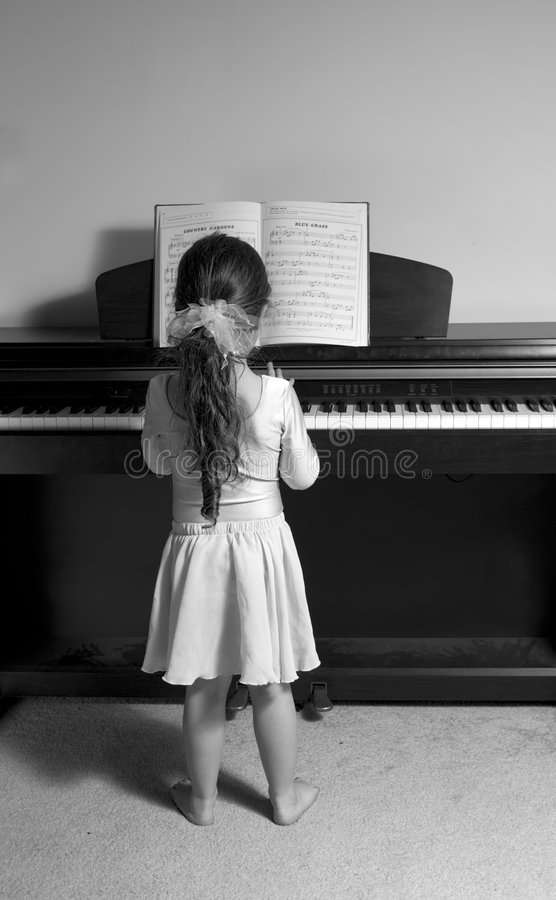 女孩钢琴使用 免版税库存照片