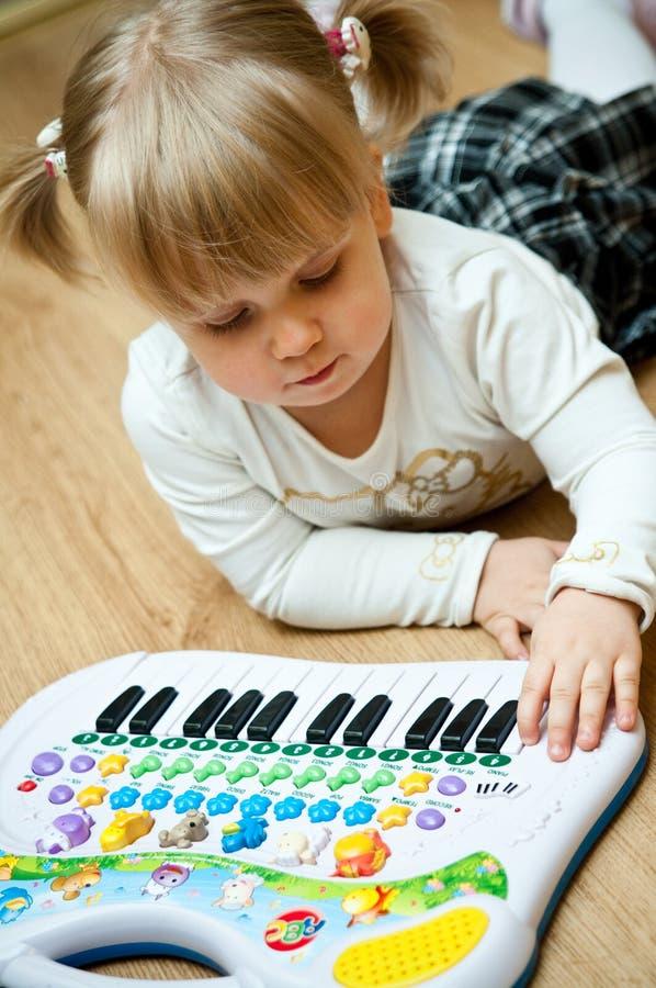 女孩钢琴玩具 免版税库存图片