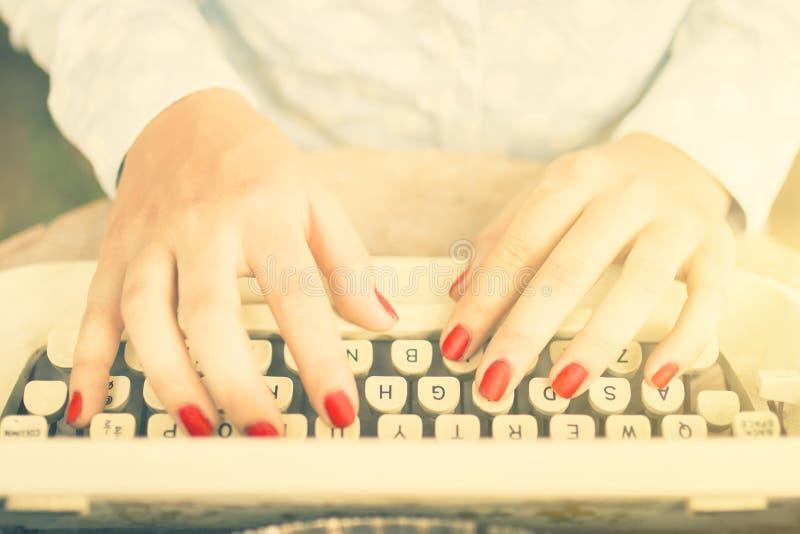 女孩键入在打字机的,葡萄酒照片作用 免版税库存照片