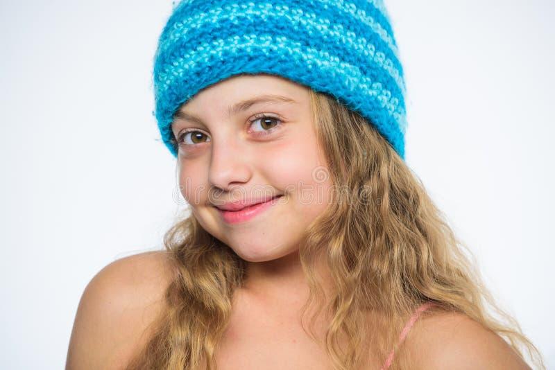 女孩长的头发愉快的面孔白色背景 孩子穿戴温暖的软性被编织的蓝色帽子 在编织和钩针编织之间的区别 免版税库存照片