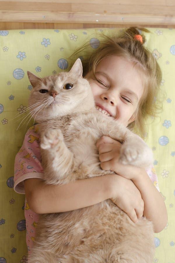 女孩闭上了她的充满喜悦的眼睛,拥抱她的宠物猫 库存照片