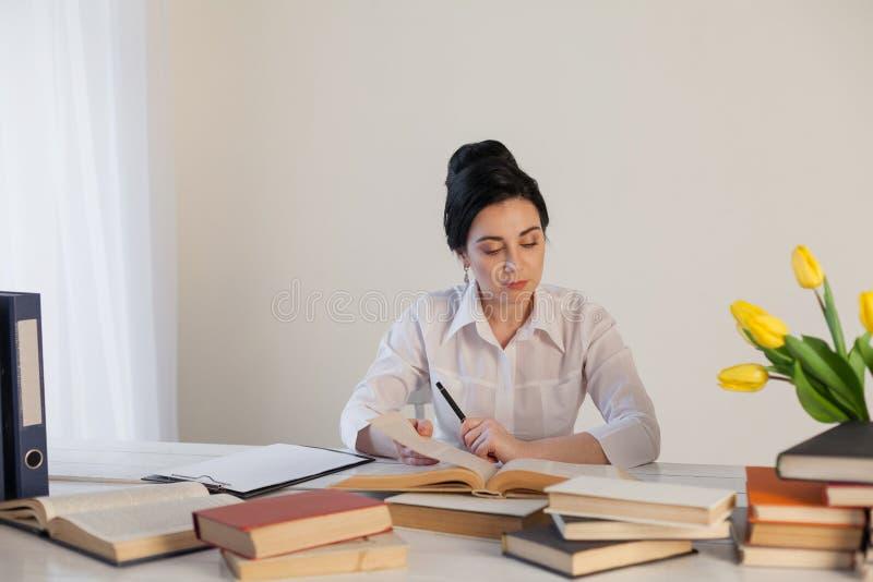 女孩阅读书在办公室事务的桌上 库存图片