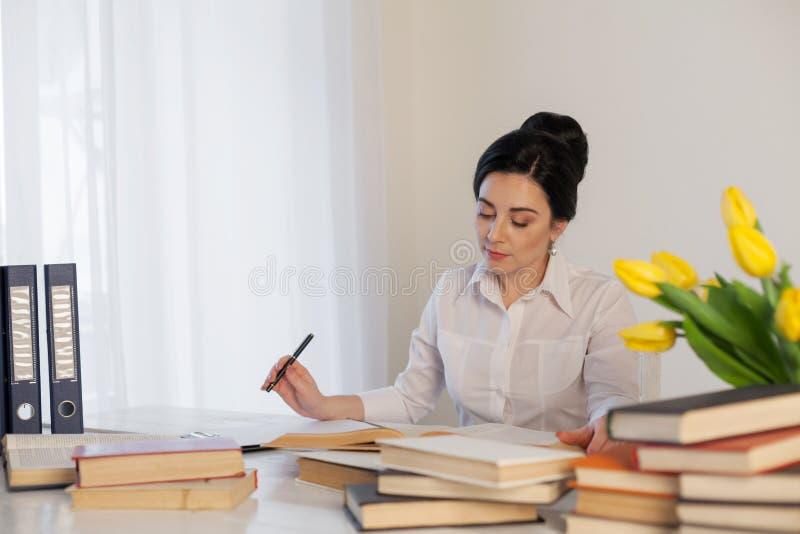 女孩阅读书在办公室事务的桌上 免版税图库摄影